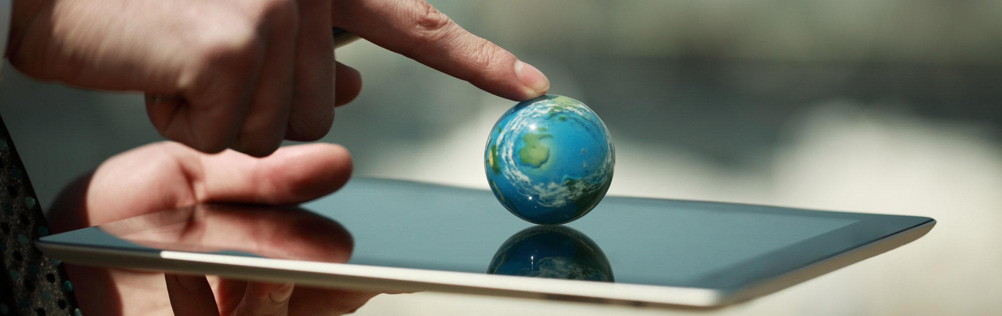A finger pointing to a small globe on top of a tablet
