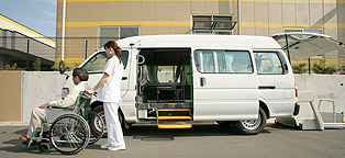 A nurse pushing a patient o a wheel chair next to a modified van for transportation